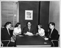Five people sit around an office table at Crowley's Department Store for Wayne University Day at Crowley's.