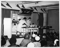 Three women give a kitchen demonstration to a group of ladies at Crowley-Milner Department Store  for Wayne University Day at Crowley's.
