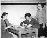 A veteran is taking a test as two women observe.