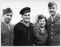 A group of veterans, men and a woman, pose for a photo.
