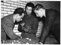 A veteran soldier instructs two men about a cog gear.