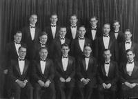 "Glee Club, c. 1925. 3rd. Row, l to r: ?,?, Owen Pauline, James Bickley,?. 2nd Row: James Gibb, George Skene,?,?,?,?. 1st Row: Dave Persons, Henry Rehn, Norman Stockmeyer, Russel Smith, Cecil Cody,""?."