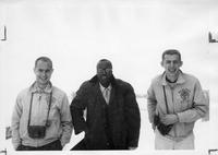 A wintery scene with three members of the Men's Glee Club.