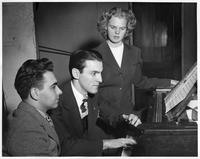 Two men and a woman at a piano.