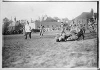 A football play in action. A player is tackled while the referee looks on.