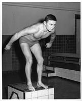 Harry Schlosser, a swimmer, readies himself on the starting block.