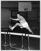 A track athlete runs some hurdles in the gym.