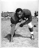 A football player, Jim Moore, #61, in a three point stance.