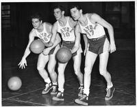 Three basketball players, numbers 18, 10, and 17, practice.