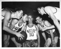 The 1938 basketball team huddles up.