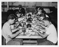The 1940 Football team shares a meal.