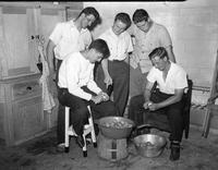Some 1940 Footballers peel potatoes.