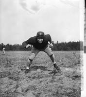 A 1940 Football player poses in a ready position.