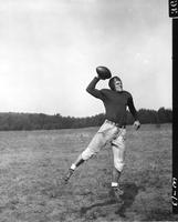 A uniformed football player, likely the quaterback, winds up to make a pass.