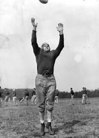 A uniformed player stretches to make a catch. It is Co-Captain Pat savage, Senior End.