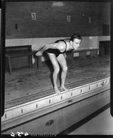 A swimmer in starting position at pool's edge.