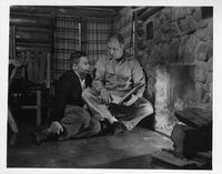 A coach and a player inspect a playbook near a fire.