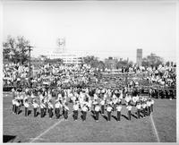 The marching band plays a number on the football field.
