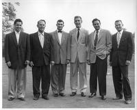 The 1955 golf team in formal attire on a putting green.