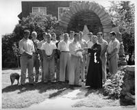 A group of men gather in front of a Madonna shrine. A priest and one man hold a Rosary.
