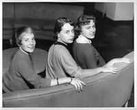 Three women pose for a shot on a couch.