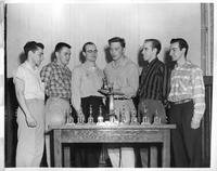Wrestling. Six men stand if front of a cache of trophies. Allan Kovan, Tom Keller, Terry Fagan, Wayne Mueller, Dick Ladson, Pete Nicholas.