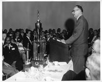 Michigan Secretary of State James Hare addresses a crowd at a trophy ceremony.