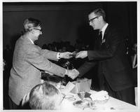 Bob Miller (Rowing) is handed an award in a bag by Dean Stewart.