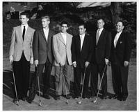 The golf team in formal attire on a putting gree showing off with what look like 2 irons.