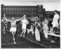 A Wayne track athlete about to cross the finish line first at a meet in front of Redford High School.