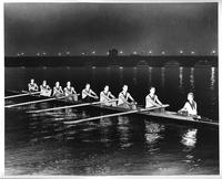 A nighttime action shot of uniformed rowers in the Detroit River with the MacArthur Bridge in the background.