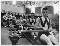 A uniformed rowing team at a workout facility.
