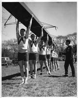 The rowing team carries their boat over their heads.
