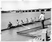 The rowing team in the water preparing to begin. The MacArthur Bridge is visible.