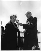 President Clarence Hilberry and a guest make some remarks at a rowing event.