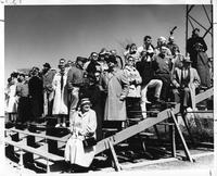 A small crowd stands on some bleachers to watch a rowing match.