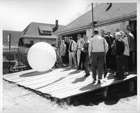 The rowing team and guests, such as Clarence Hillberry, surround a weather balloon.