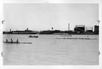The rowing crew on the Detroit river during a race with a chase boat in pursuit. Other vessels are visible, as is industry on the riverbanks.