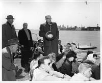 Clarence Hilberry makes an announcement at a rowing event. The Detroit River, Detroit Skyline, and Ambassador Bridge are visible in background.