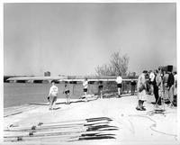 The 1958 rowing team/crew lifting their boat towards the river.