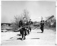 The 1958 rowing team/crew carrying their oars towards the river.