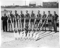 The 1958 rowing team/crew pose with their oars by the river.