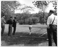 An athlete approaches the finish line while men record his time with a stopwatch and clipboard.