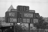 1985 football action shot at Homecoming game versus Northwood. The scoreboard with Fisher Building in the background.