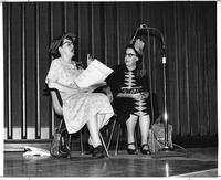 Two women perform a scene on stage.