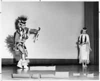 A man and woman in traditional Native American attire dance.