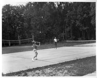 A man and a woman play doubles tennis.