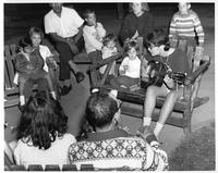 Some young children gather around the adults for some guitar music and a sing-a-long.