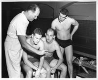 Three swimmers and a coach/trainer examine their time on a stopwatch.