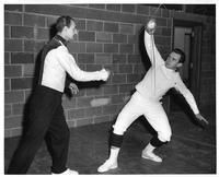 Coach Danosi trains with a fencer.